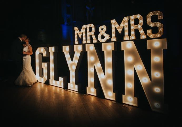 bride and groom kiss in front of wedding light up letters
