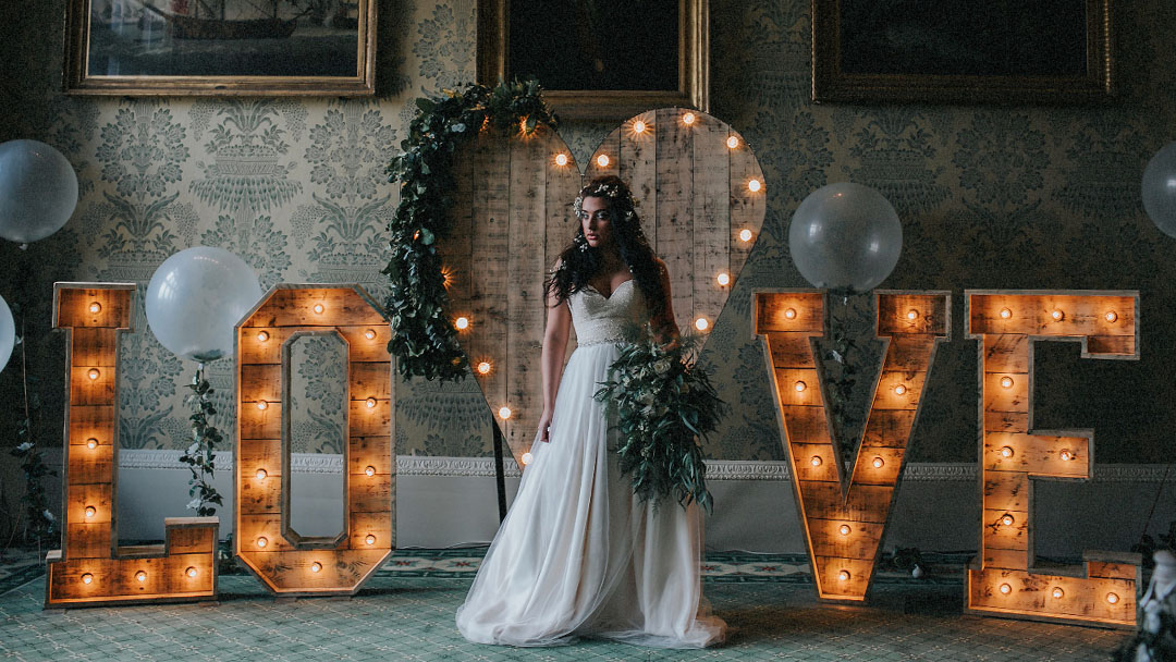 BRIDE STOOD WITH RUSTIC LIGHT UP LOVE LETTERS BY THE WORD IS LOVE