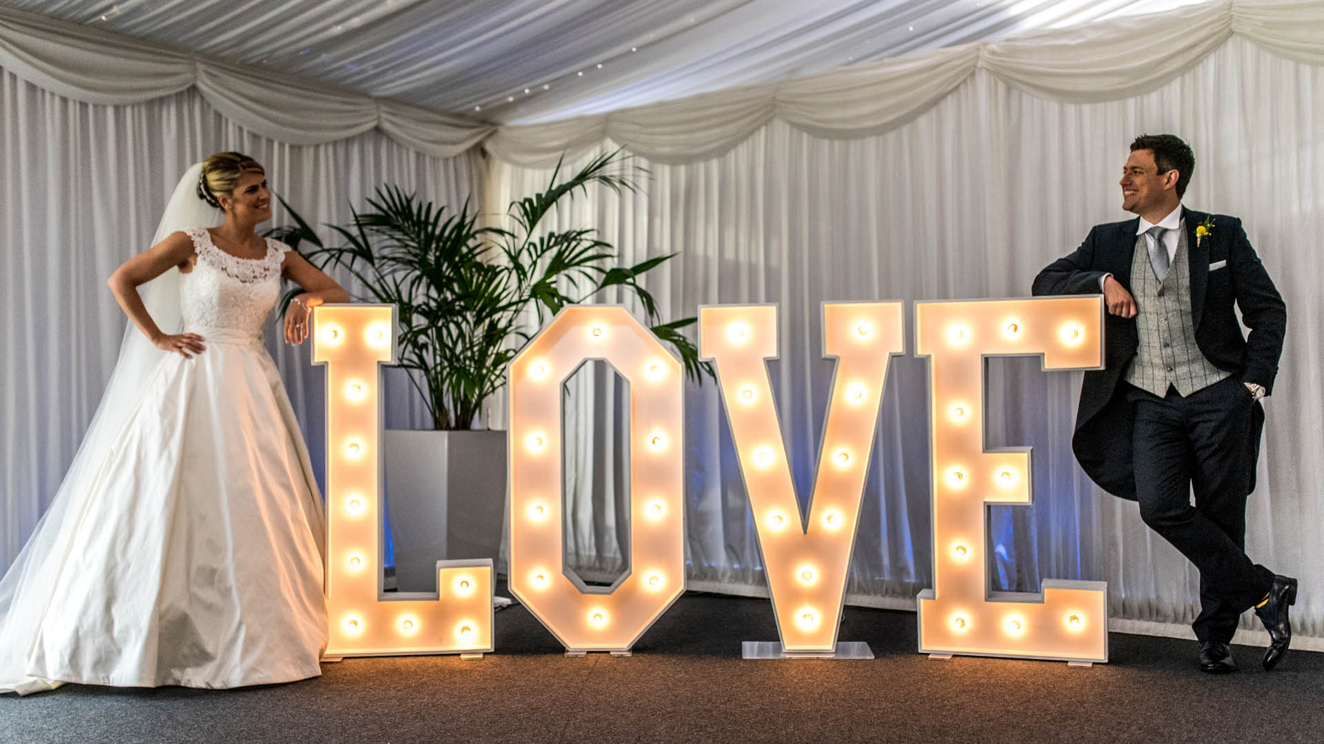 BRIDE AND GROOM WITH LIGHT UP LOVE LETTERS BY THE WORD IS LOVE