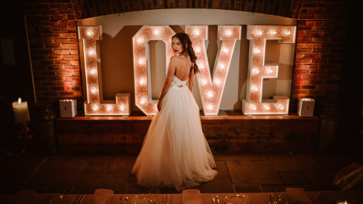 bride standing with Rose Gold Glitter Love letters at Owen House Wedding barn