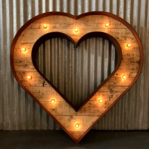Rusty Light up Kissing Heart against a Corrugated Metal Backdrop