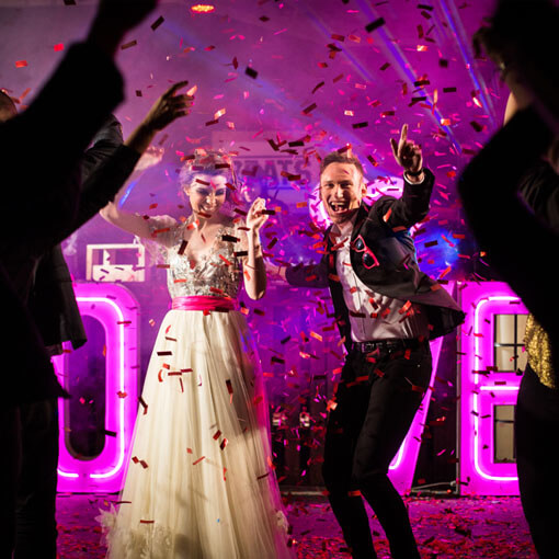 bride and groom dancing in front of neon light up ltter love sign
