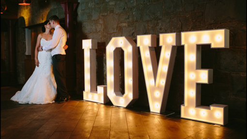 COUPLE STANDING WITH THE LIGHT UP LOVE LETTERS
