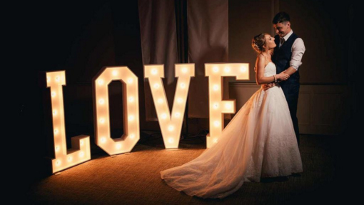 couple kissing next to the word is love light up letters