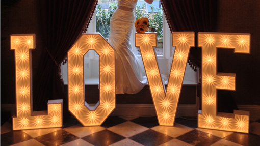 bride standing with sparkle light up love letters on chequered floor