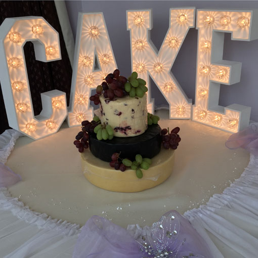 light up letter cake sign with cheese wedding cake
