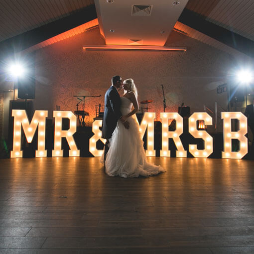 mr and mrs b dancing in front of their light up letters