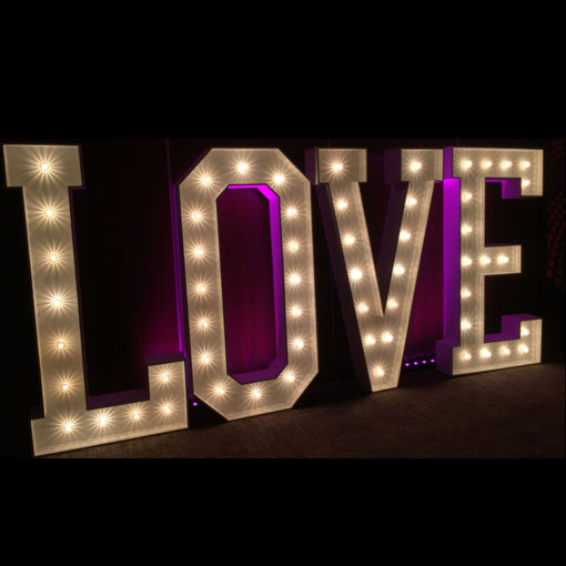 uplighting the word is love with purple led batons