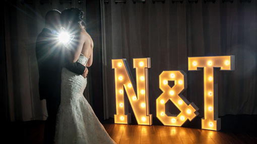 naomi and tom dance next to wedding light up letters intials