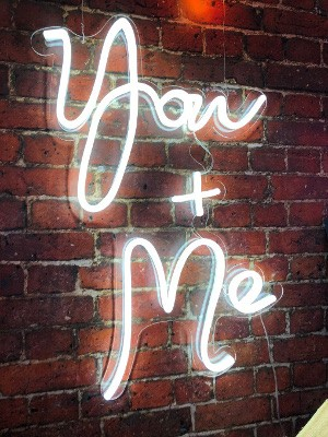 White YOU+ME neon Sign to hire on Brick background